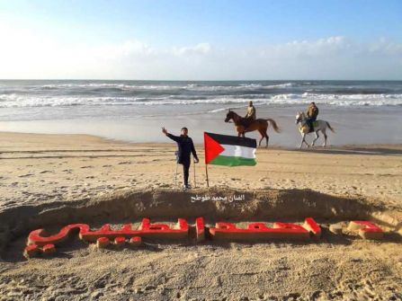 فنان فلسطيني ينحت اسم أحمد  الطيبي في رمل بحر غزة